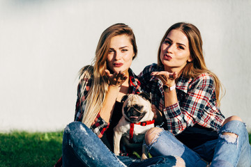 Two beautiful smiling sisters twins and dog pug sitting and sending an air kiss on green grass in the summer park