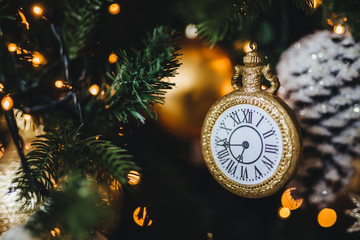Picture of decorated New Year or Christmas tree with garlands and baubles. Decoration in form of clock symbolizes starting new year. Holidays, celebration, winter concept.