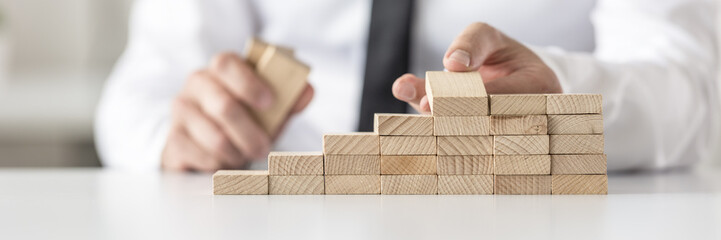 Closeup of businessman arranging wooden pegs into a staircase