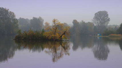 beautiful foggy morning on the lake with the camping fishermen in the distance on the shore, autumn landscape. 16:9 ratio