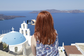 Woman taking a picture of the blue dome Church St. Spirou in Firostefani on the island of Santorini, Greece