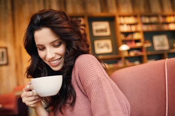 pretty woman drinking coffee in a cafe. Pleasure time