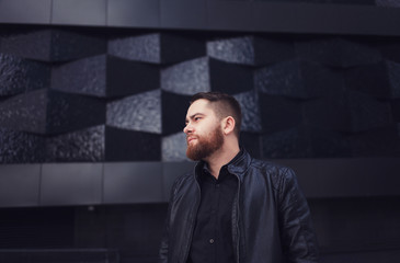 Portrait of a handsome bearded man in a leather jacket on wall background