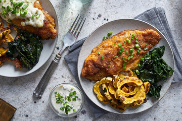 panfried catfish dinner with squash and spinach in flat lay compositon