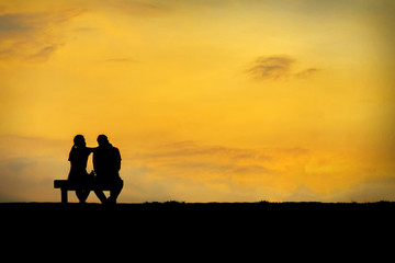 Back view of a couple silhouette sitting on Chair at colorful sunset on background
