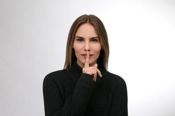 Hübsche Frau mit Finger auf den Lippen