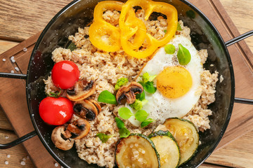 Frying egg with oatmeal, egg, mushrooms and vegetables on table