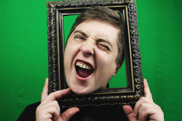 Young man with picture frame filled with excitement. Man on chroma key, emotions green background. Man holding a vintage frame