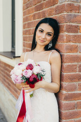 Attractive female bride wears wedding white dress, holds bouquet, stands near brick wall, has appealing appearance. Elegant young woman with make up, has charming smile celebrates her wedding