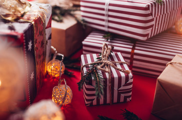 Gift boxes decorated with fir branches on red background.