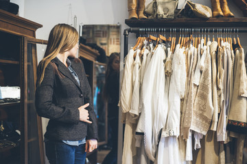 Young woman trying a new jacket in a vintage store