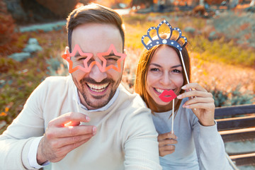 Happy couple in love having fun outdoors with party set mask.