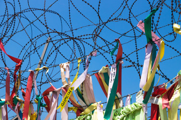 colourful ribbons tied at barbed wire at a fence at the demilitarised zone DMZ at the freedom bridge, South Korea, Asia