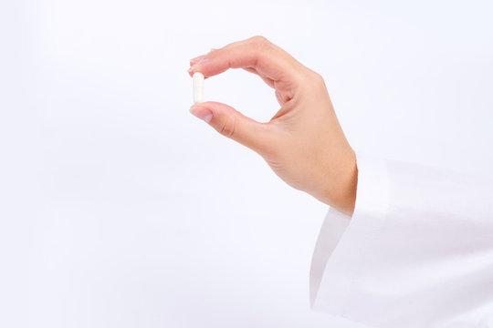 hand of nurse doctor holding white capsule