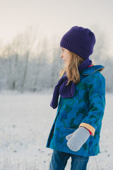 a girl looks into a snowy field on a winter day