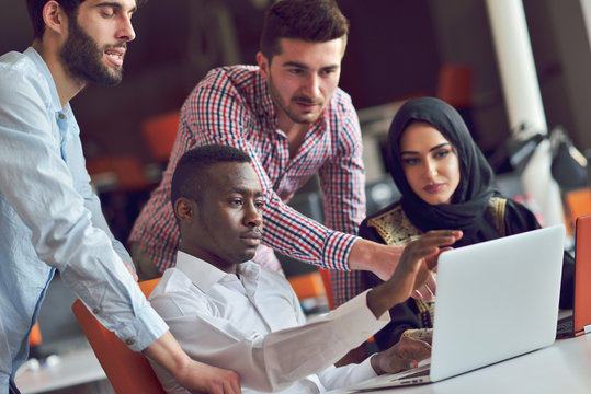 Multiracial contemporary business people working connected with technological devices like tablet and laptop