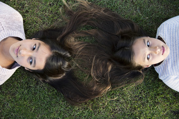 Two girls laying on grass