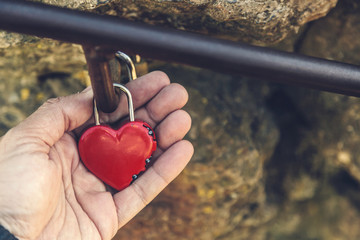 Hand Holding a Red Heart Shaped Padlock