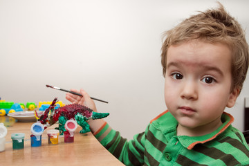 Little boy concentrating whilst painting a toy dinosaur on the desk