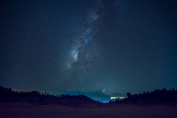 Long exposure and High ISO (800) shot of star and milky way over the silhouette mountain and rice field at night.