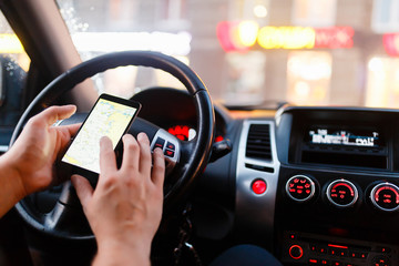 Closeup of smartphone in hand of young man sitting behind the wheel of modern car. In the background street lights and cars. Man paves way in gps. On screen of smartphone map of area