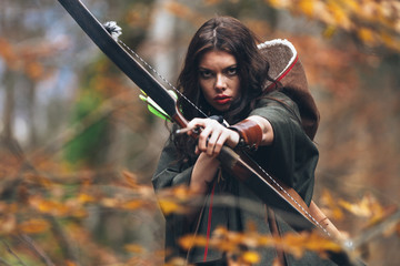portrait of a beautiful brunette woman taking aim with bow and arrow