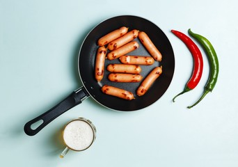 Beer and sausages fried in a frying pan, a top view, blue background.