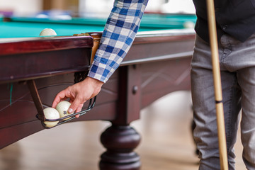 The player pulls out the billiard ball from the pocket of the table