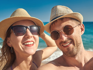 Joyful man and woman in sunglasses are making selfie photo on the beach against the sea.