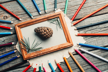 Christmas composition, photo frame on wooden table with tree branches with pencils and cones