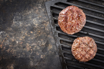 Barbecue wagyu Hamburger as top view on a grillage with copy space left