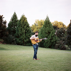 Bearded man with a guitar standing in a park