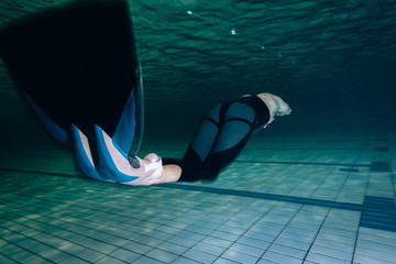 Free diver swimming with monofin in the pool underwater
