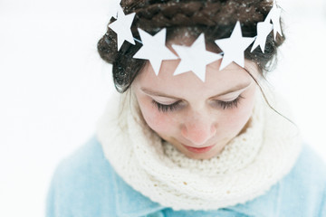 Little girl wearing a star wreath in the snow
