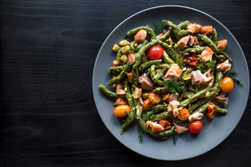 Salmon and spinach spaghetti served on wooden background with blank space .