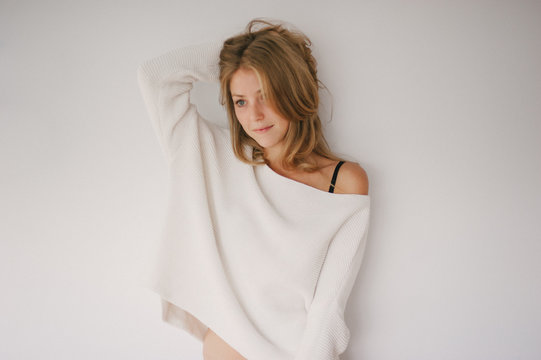 Attractive woman in oversized knit sweater with white background