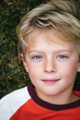close-up, overhead portrait of a boy lying in the grass