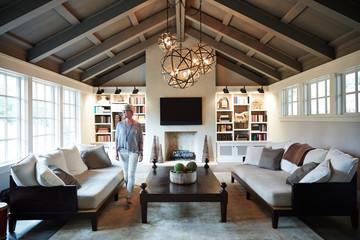 Mature woman walking through luxury living room