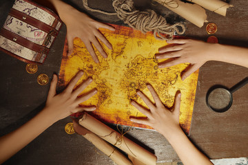 Top view of four hands on map of pirates treasure