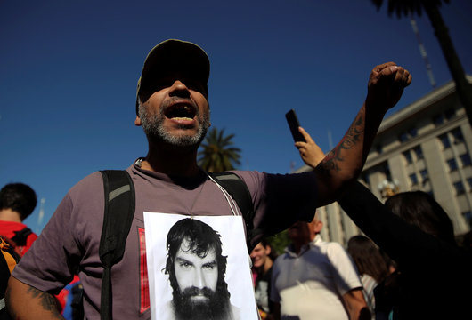 A man shouts slogans as he shows a a portrait of Santiago Maldonado during a demonstration in Buenos Aires