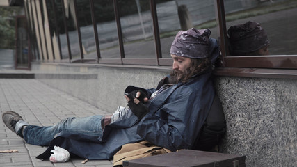Bearded unemployed begging man sitting in street while using smartphone
