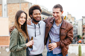 Portrait of happy young friends drinking bottles of beer on a rooftop.