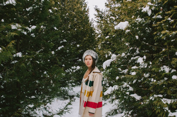 Attractive young mixed asian girl wearing wool jacket and fur hat in middle of forest in snow