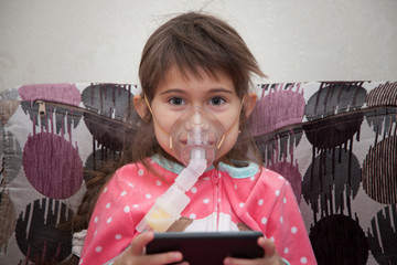 Little girl is wearing a breathing mask and playing games on mobile phoneShe is sick. Girl is inhaling medicine through inhaler at home. She dressed in dotted pink pajamas. Her disease is pneumonia.