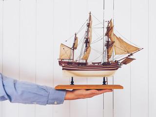 Man holding antique wooden ship replica.