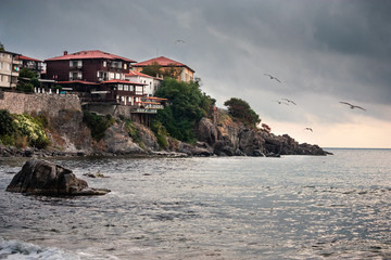 Foto op Plexiglas Stad aan het water Coastal landscape - the rocky seashore with seagulls and houses, town of Sozopol on the Black Sea coast in Bulgaria
