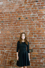 Young woman standing in front of brick wall