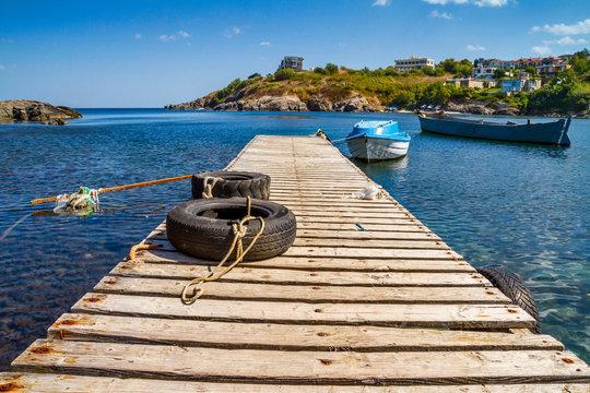 Coastal landscape - the wooden pier and boats in rocky bay, near city of Sozopol on the Black Sea coast in Bulgaria
