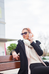 Stylish young woman having a call chat outdoor on wooden bench.
