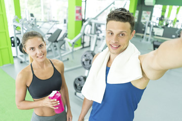 The sportsman and sportswoman make a selfie in the sport center